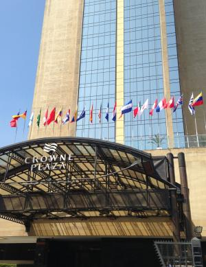 The front awning of the Crowne Plaza Hotel, displaying several national flags