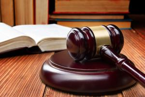 Law book and judge's gavel resting on a wooden table