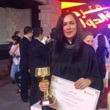 Basema Younes holding her award