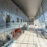 Interior hall of the DECC with light shining through glass wall