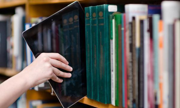 A hand reaching an ebook reader down from a bookshelf